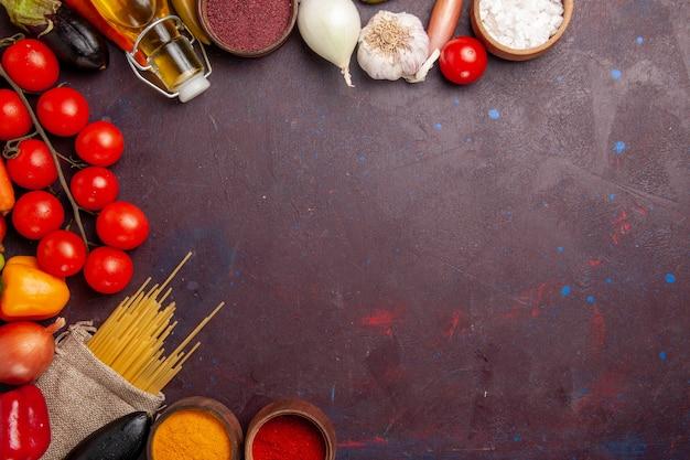 어두운 공간에서 원시 이탈리아 파스타와 조미료가 들어간 상위 뷰 신선한 야채