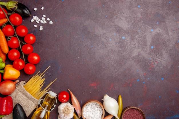 Vista dall'alto di verdure fresche con pasta italiana cruda sullo spazio buio
