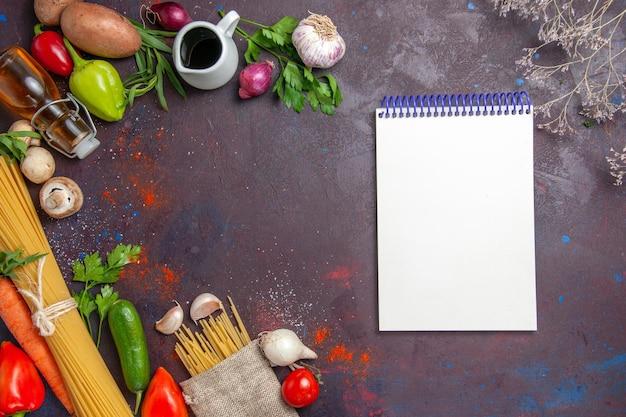 暗い表面の熟した食品の食事のサラダに生パスタとメモ帳を備えた上面図の新鮮な野菜