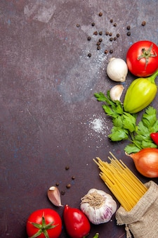 Top view of fresh vegetables with raw pasta on black