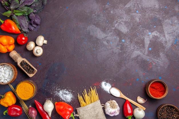 暗い表面の食事食品サラダパスタに生パスタと新鮮な野菜の上面図