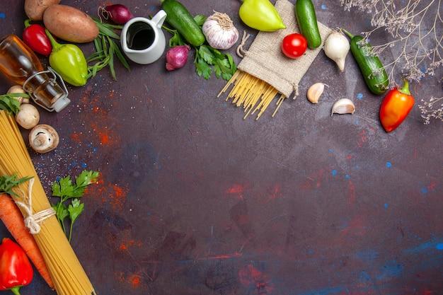 暗い表面に生パスタを添えた新鮮な野菜の上面図熟した食品の食事サラダ