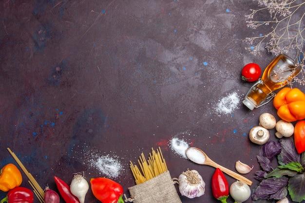 暗い表面のサラダ健康食品の食事に生パスタと新鮮な野菜の上面図