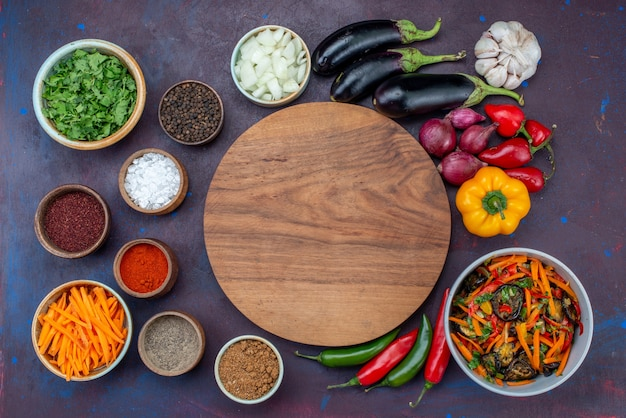 Vista dall'alto di verdure fresche con insalata e condimenti sullo spuntino di verdure del pasto dell'insalata della scrivania scura