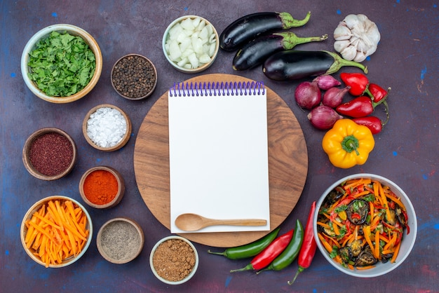 Vista dall'alto di verdure fresche con blocco note di insalata e condimenti sullo spuntino di verdure del pasto dell'insalata dello scrittorio scuro