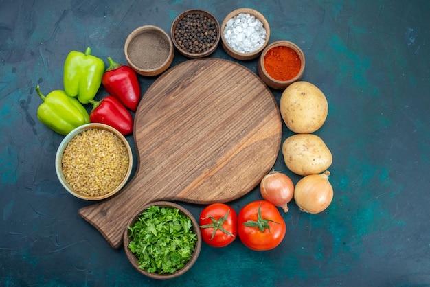 Вид сверху свежие овощи с приправами и зеленью на темно-синей поверхности