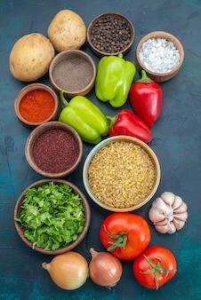 Вид сверху свежие овощи с приправами и зеленью на темно-синем столе