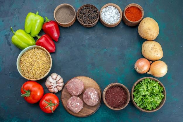 紺色の表面に調味料と緑のある新鮮な野菜の上面図