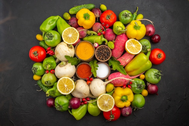 Vista dall'alto verdure fresche con condimenti sullo sfondo scuro