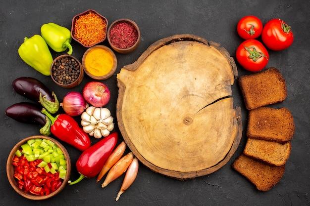 Vista dall'alto verdure fresche con condimenti e pagnotte di pane scuro su un pasto salutare per insalata di pane da scrivania scuro