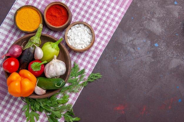 Vista dall'alto verdure fresche con condimenti su alimenti salutari per insalata matura di superficie scura