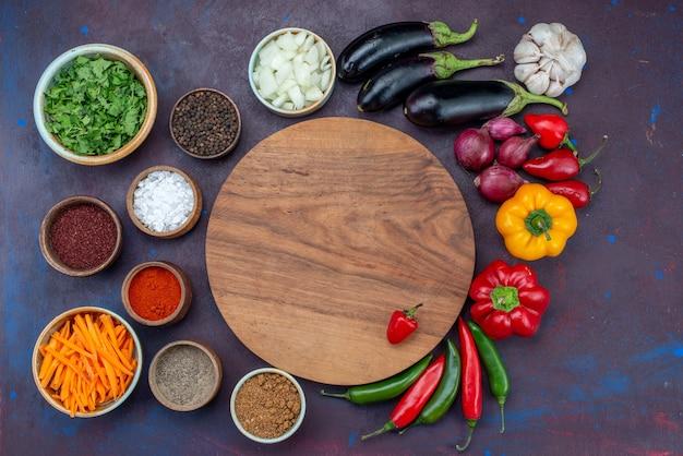Vista dall'alto di verdure fresche con condimenti e verdure sullo spuntino di verdure del pasto dell'insalata della scrivania scura