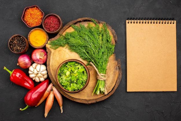 Vista dall'alto verdure fresche con condimenti e verdure sulla superficie scura insalata salute pasto maturo vegetale