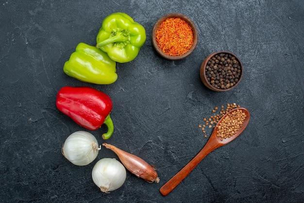 Top view fresh vegetables with seasonings on grey space