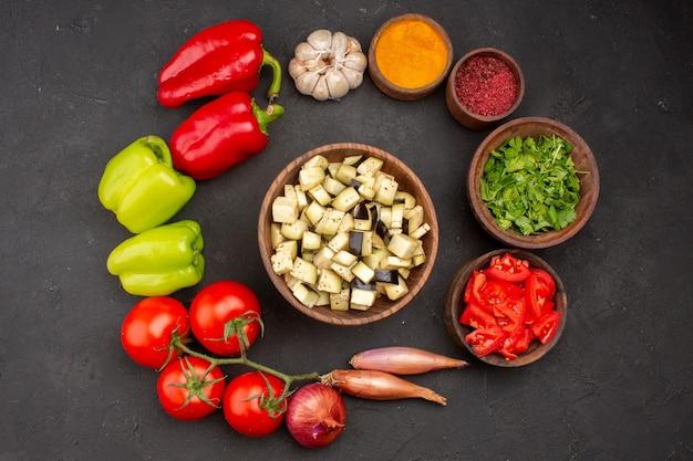Vista dall'alto di verdure fresche con condimenti su verdure di farina di salute insalata superficie grigia