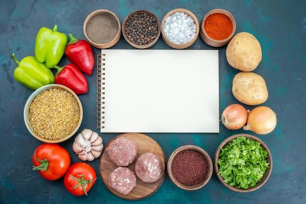 紺色の表面に調味料の肉と緑のある新鮮な野菜の上面図
