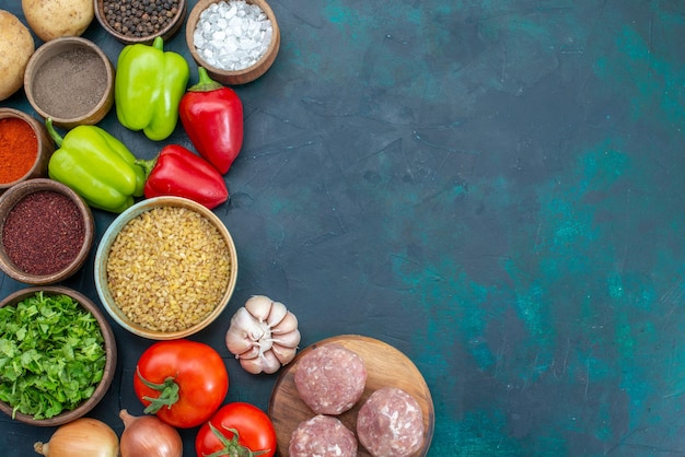 Vista dall'alto verdure fresche con condimenti carne e verdure sulla scrivania blu scuro