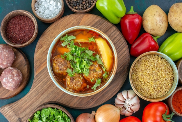 紺色の机の上に調味料肉汁と緑と新鮮な野菜の上面図