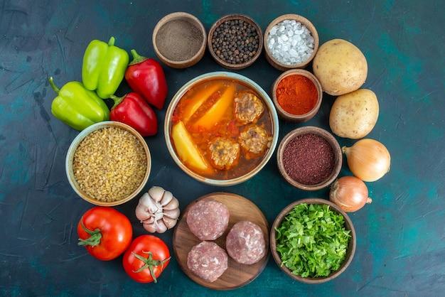 Vista dall'alto verdure fresche con condimenti zuppa di carne e verdure sulla superficie blu scuro