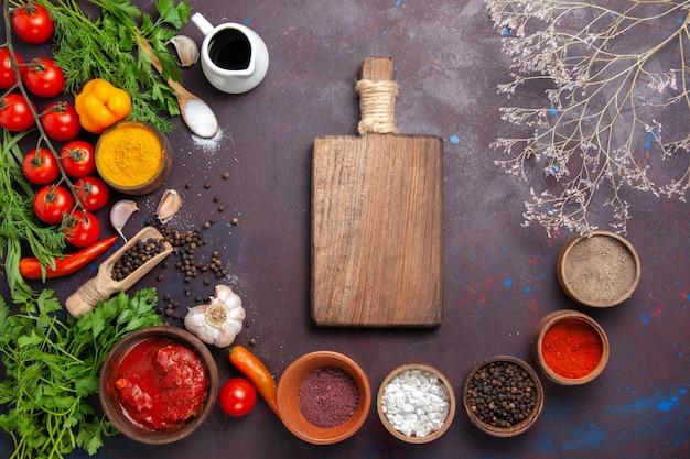 暗い空間に調味料と新鮮な野菜の上面図