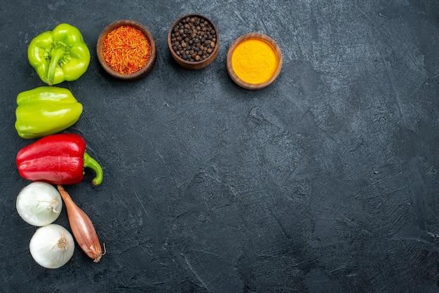Вид сверху свежие овощи с приправами на сером пространстве