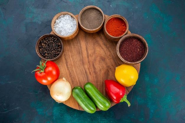 濃紺の背景に調味料と新鮮な野菜の上面図。