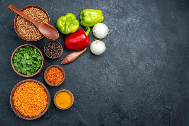 灰色の空間に調味料と新鮮な野菜の上面図