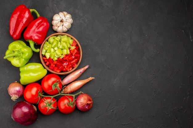 Вид сверху свежие овощи с приправами на сером фоне салат здоровая еда овощной
