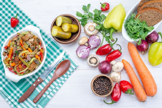 Top view of fresh vegetables with sliced meat dish and bread loafs on light, vegetable food meal meat
