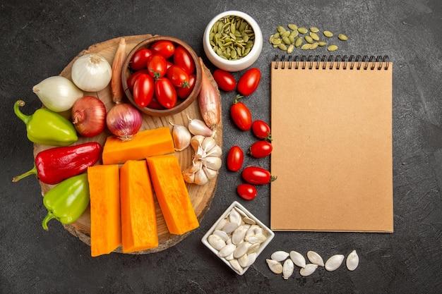 Вид сверху свежие овощи с нарезанной тыквой и чесноком на сером фоне цветных семян свежих спелых салатов