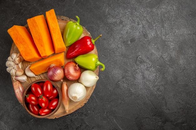 Vista dall'alto verdure fresche con zucca a fette sullo sfondo grigio scuro colore maturo fresco