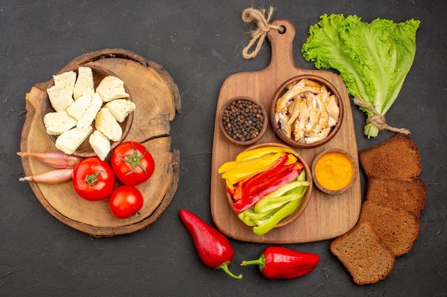 Top view of fresh vegetables with white cheese and black bread on black