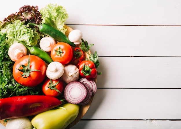 Top view of fresh vegetables on wooden surface