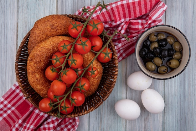 Top view of fresh vine tomatoes on a bucket with bagels on a sack cloth with olives on a bowl and eggs on a grey wooden background