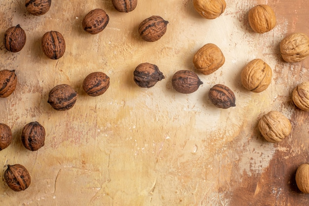 Top view of fresh walnuts lined on a wooden desk