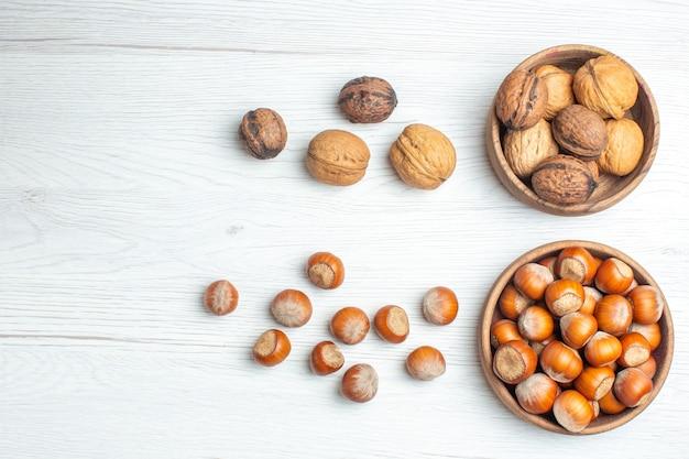 Вид сверху свежие грецкие орехи с фундуком на белом столе