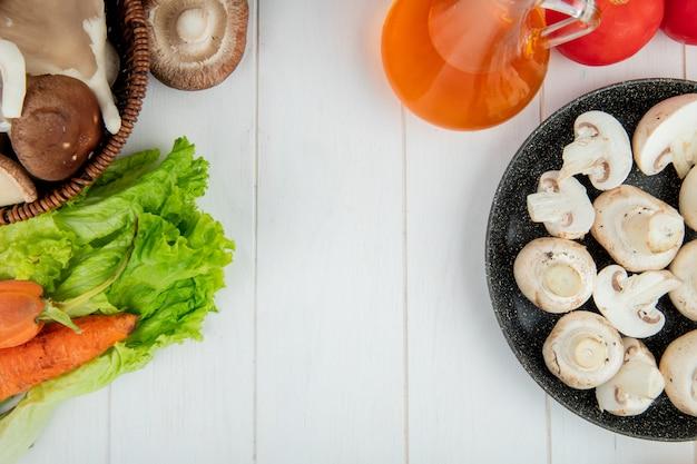 Vista superiore dei funghi bianchi freschi su un piatto e bottiglia di carote fresche di olio d'oliva su bianco con lo spazio della copia