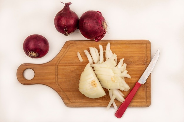 Vista dall'alto di cipolla bianca fresca su una tavola di cucina in legno con coltello con cipolle rosse isolato su una superficie bianca