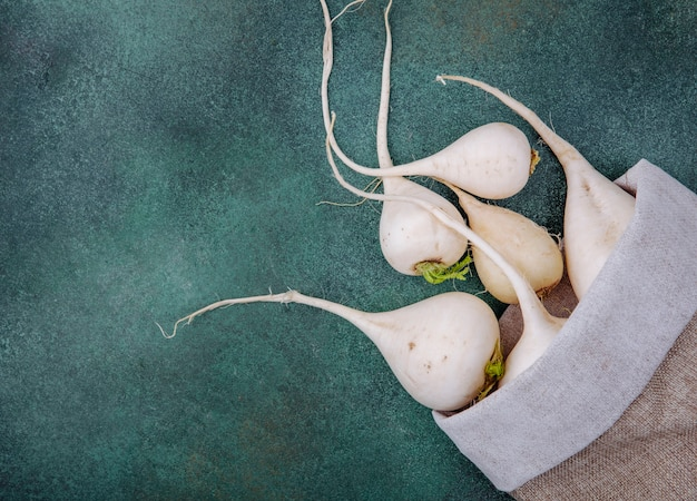 Vista dall'alto di barbabietole fresche ortaggi a radice bianca su un sacchetto di tela da imballaggio su uno sfondo verde con spazio di copia