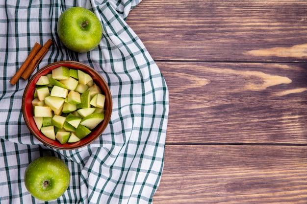 Vista superiore della mela intera fresca con un'insalata di mele sulla ciotola rossa sulla tovaglia controllata su legno con lo spazio della copia