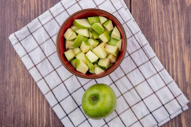 Vista dall'alto della mela intera fresca con fette di mela tritate sulla ciotola rossa sulla tovaglia e sul legno controllati