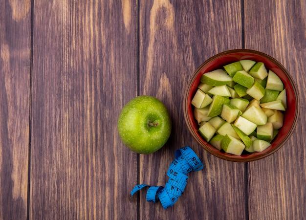Vista dall'alto della mela intera fresca con fette di mela tritate sulla ciotola rossa su legno con spazio di copia