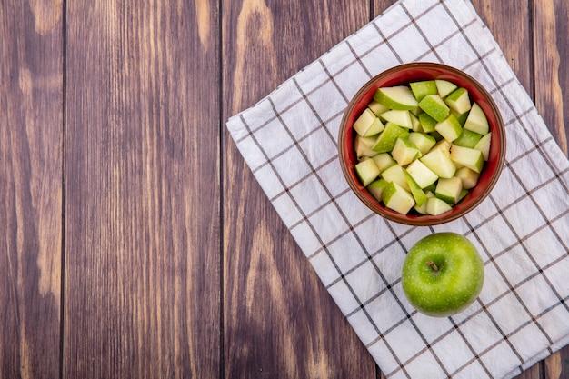 Vista dall'alto della mela intera fresca con fette di mela tritate sulla ciotola rossa sulla tovaglia controllata e legno con lo spazio della copia