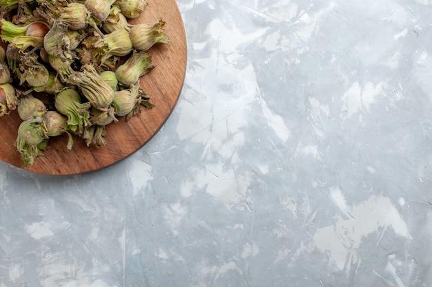 Vista dall'alto nocciole intere fresche con bucce sulla scrivania bianco chiaro nocciola noce albero pianta
