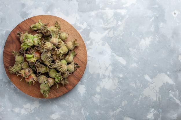 上面図白いデスクナットヘーゼルナッツクルミの木の皮と新鮮な全体のヘーゼルナッツ 無料写真
