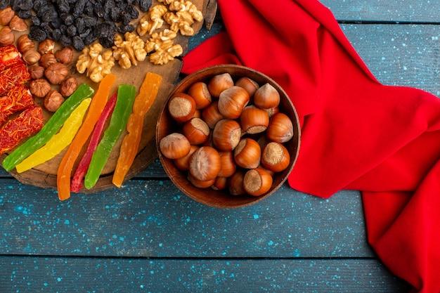 Vista dall'alto di nocciole intere fresche con noci e gelatine sulla scrivania blu
