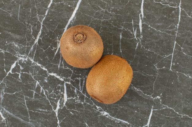 Top view of fresh whole kiwi on black stone.