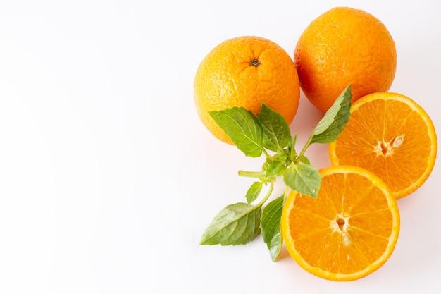 トップビューフレッシュオレンジ全体のジューシーで酸っぱい、白い背景の緑の葉と酸っぱいエキゾチックな柑橘系色の果物