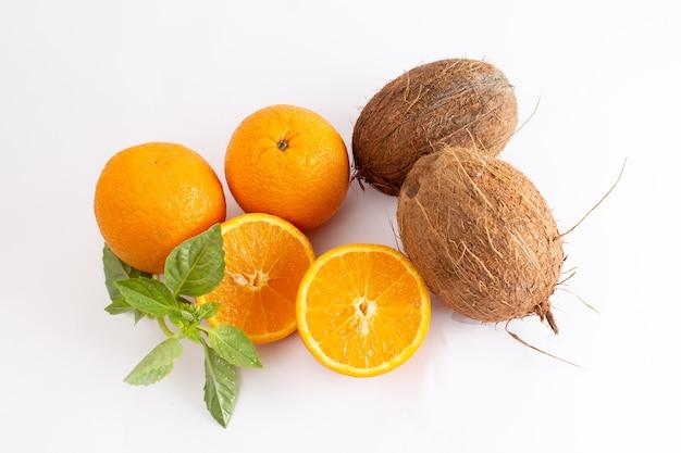 Vista dall'alto arance fresche intere succose e aspre con noci di cocco sullo sfondo bianco agrumi esotici colore frutta