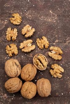 Вид сверху свежие целые грецкие орехи в скорлупе и вымытые на коричневом